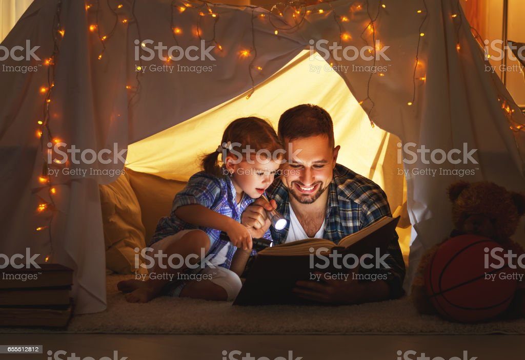 happy family father and child daughter reading a book  in  tent at home stock photo