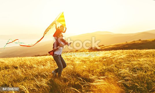istock happy family father and child daughter run with  kite on meadow 841348232