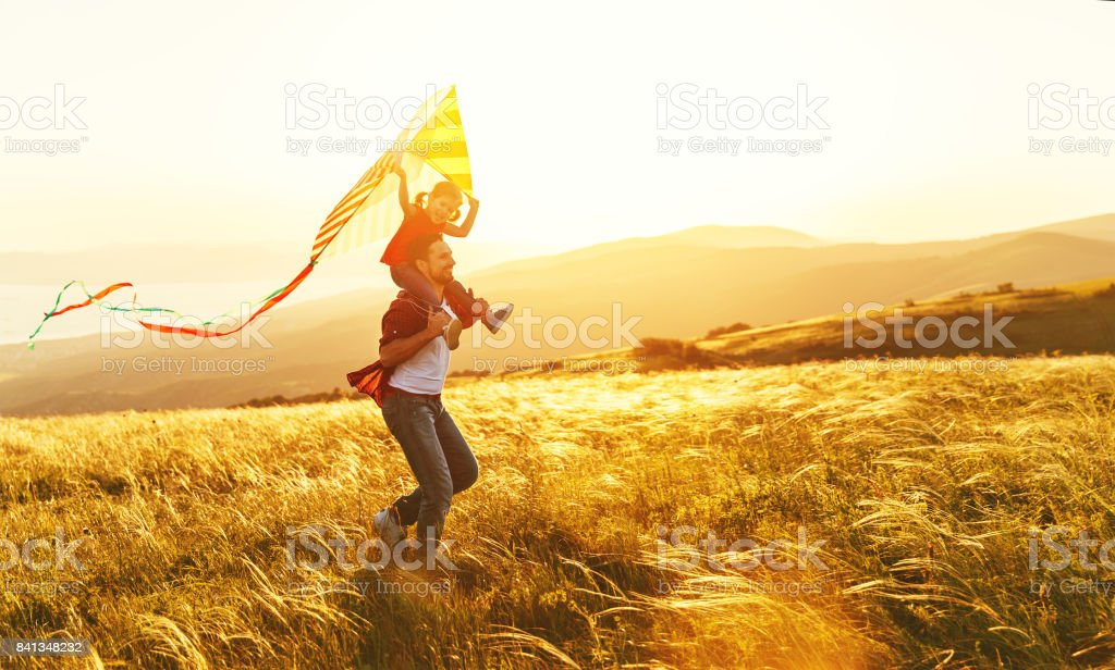 happy family father and child daughter run with  kite on meadow stock photo