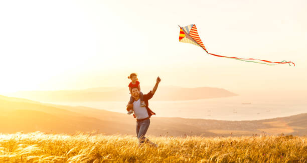 happy family father and child daughter run with  kite on meadow - foto stock
