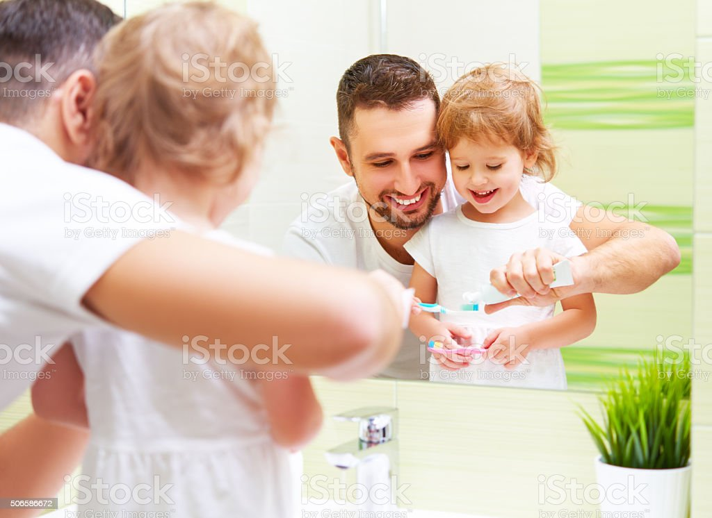 Happy family father and child girl brushing her teeth stock photo