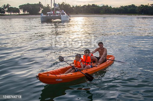 Singapore - CIRCA JULY, 2017 : Happy Family father and child on canoeing or kayaking at sea island at Singapore.