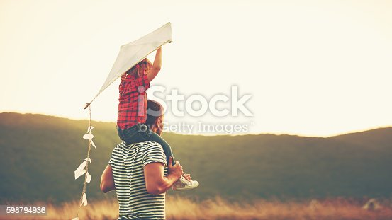 istock happy family father and child on meadow with a kite 598794936