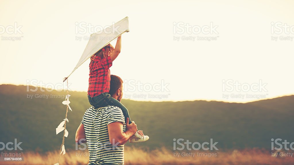 happy family father and child on meadow with a kite - foto de acervo