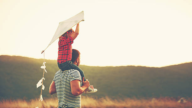 happy family father and child on meadow with a kite - insouciance photos et images de collection