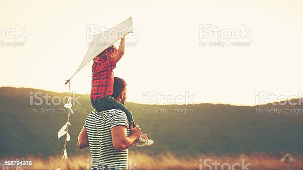 happy family father and child on meadow with a kite in the summer on the nature