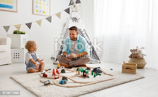 184659330 istock photo happy family father and child son playing   in toy railway in playroom 910871690