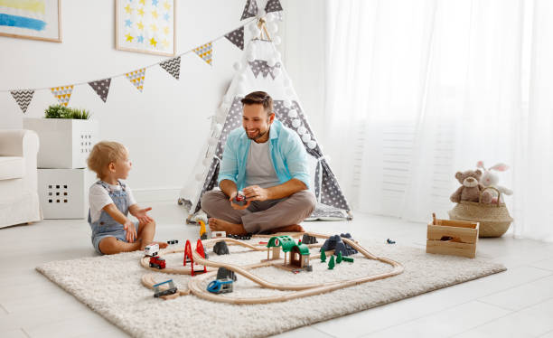 happy family father and child son playing   in toy railway in playroom stock photo