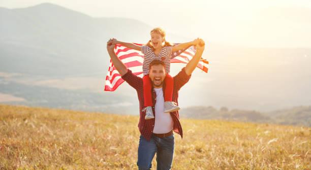 happy family father and child  with flag of united states enjoying  sunset on nature - family 4th of july zdjęcia i obrazy z banku zdjęć