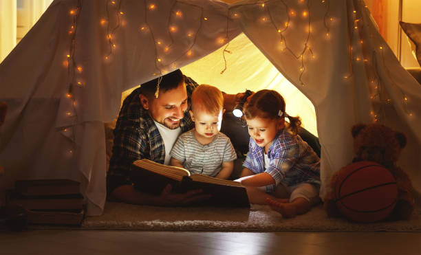 happy family father and children reading a book  in  tent at home - kinder lesezelt stock-fotos und bilder