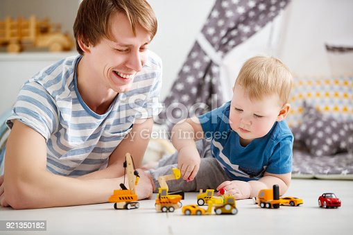 540396126istockphoto happy family father and son playing in toy car in playroom 921350182