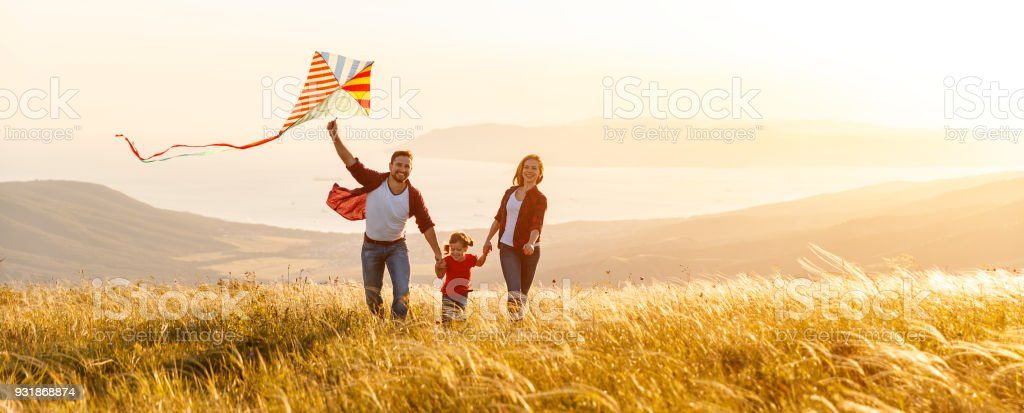 Glückliche Familie Vater, Mutter und Kind Tochter starten einen Drachen auf Natur bei Sonnenuntergang – Foto