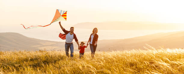 Happy family father,  mother and child daughter launch a kite on nature at sunset - foto stock