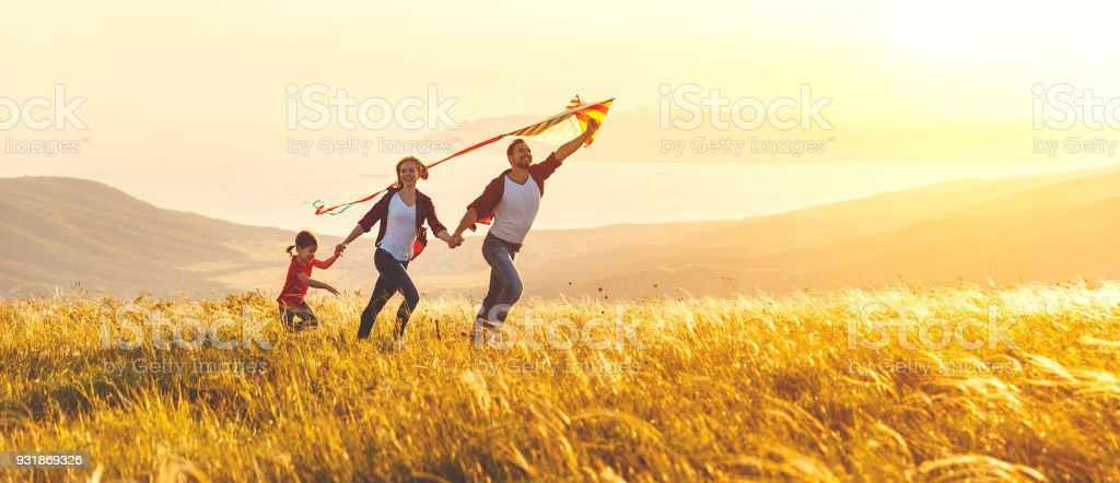 Happy family father,  mother and child daughter launch a kite on nature at sunset - fotografia de stock