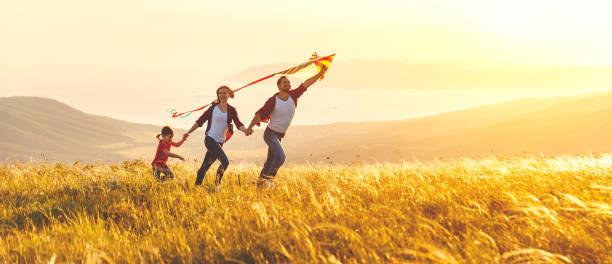 lycklig familj far, mor och barn dotter lansera en kite på naturen vid solnedgången - summer field bildbanksfoton och bilder