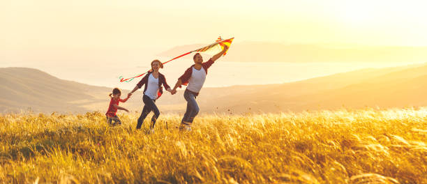happy family father,  mother and child daughter launch a kite on nature at sunset - happy family zdjęcia i obrazy z banku zdjęć