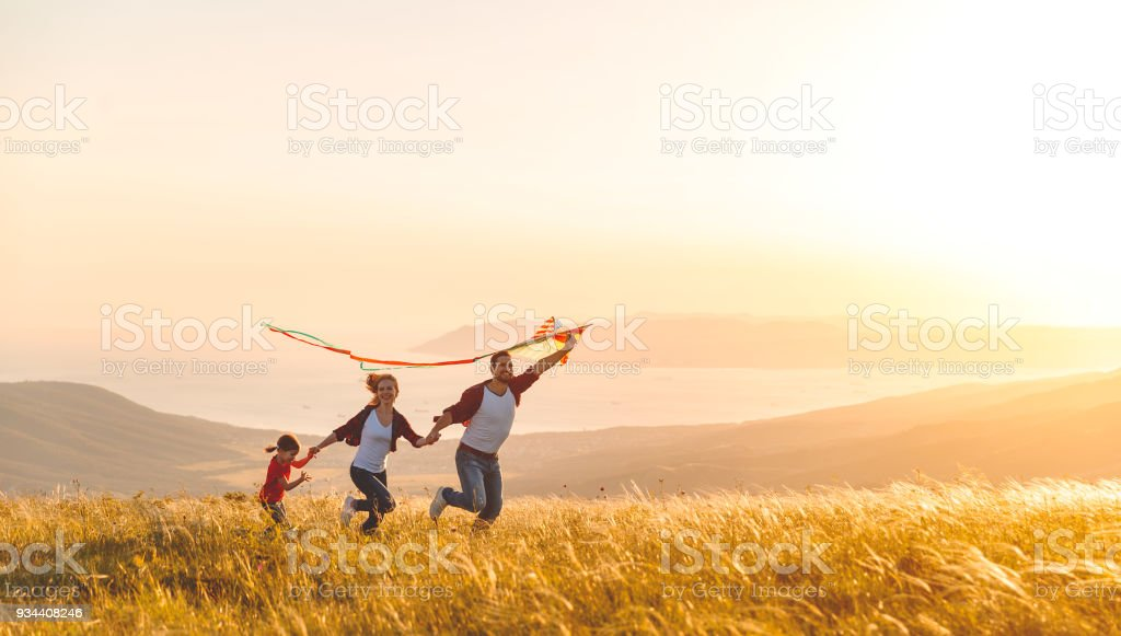 Happy family father,  mother and child daughter launch a kite on nature at sunset stock photo