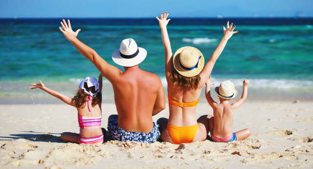 happy family father, mother and children backs on  beach at sea happy family father, mother and children backs on the beach at sea swimwear stock pictures, royalty-free photos & images