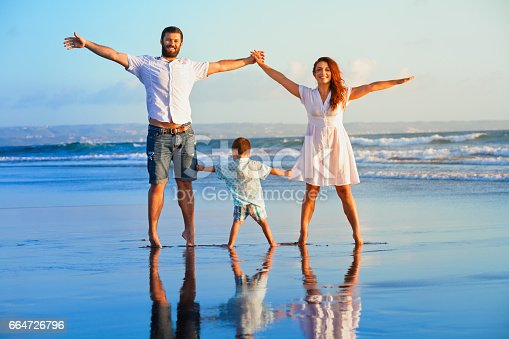 929671306 istock photo Happy family - father, mother, baby on summer beach vacation 664726796