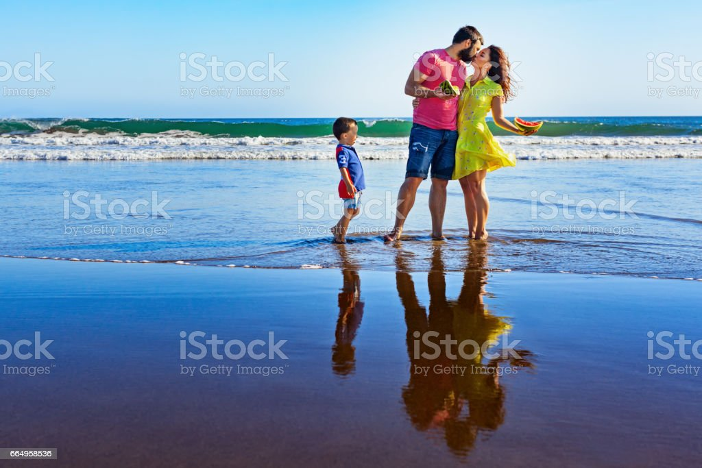 Happy family - father, mother, baby on summer beach vacation stock photo