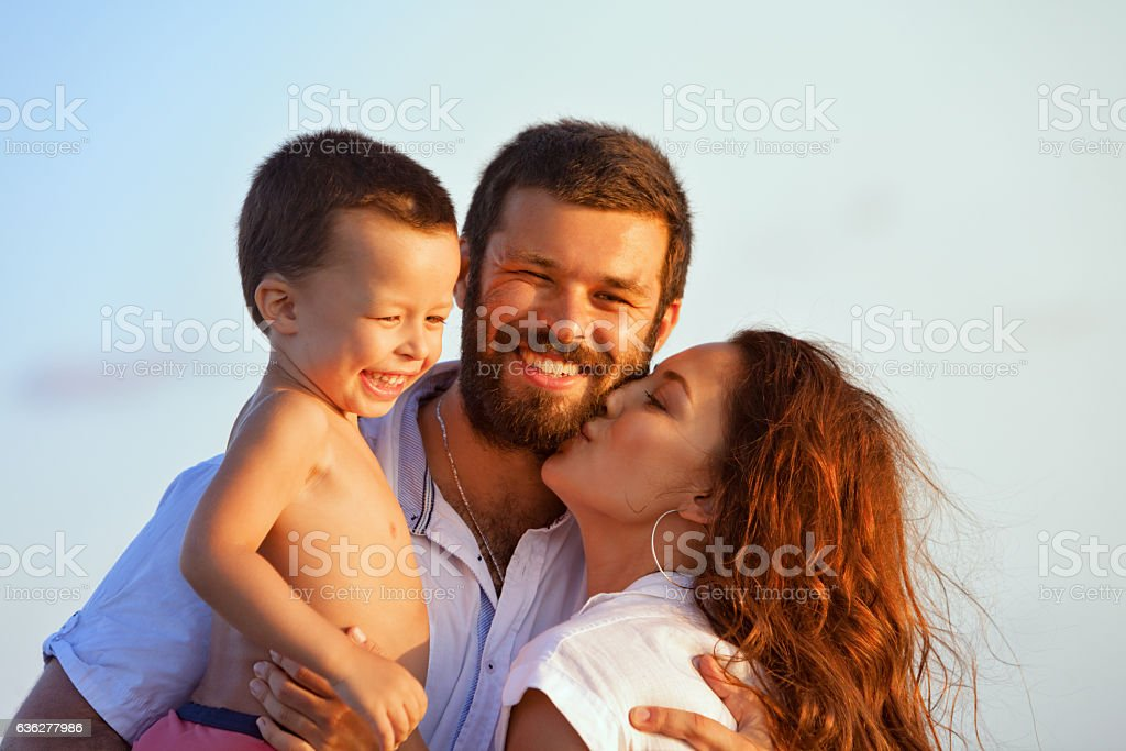 Happy family - father, mother, baby on sunset beach stock photo