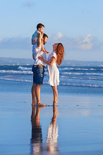 happy family father, mother, baby son on sea beach holiday - pool schritte stock-fotos und bilder
