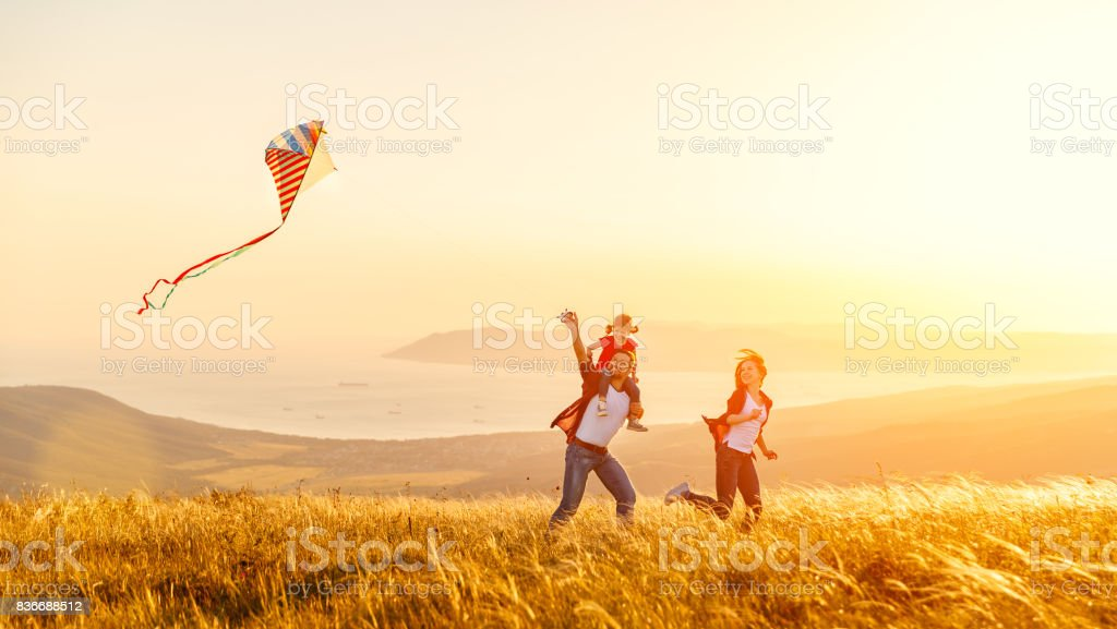 Happy family father of mother and child daughter launch a kite on nature at sunset royalty-free stock photo