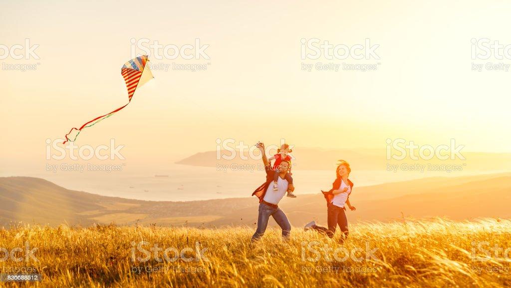 Feliz familia padre hija madre e hijo lanzar una cometa en naturaleza al atardecer foto de stock libre de derechos