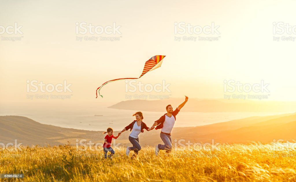 Happy family father of mother and child daughter launch a kite on nature at sunset foto stock royalty-free