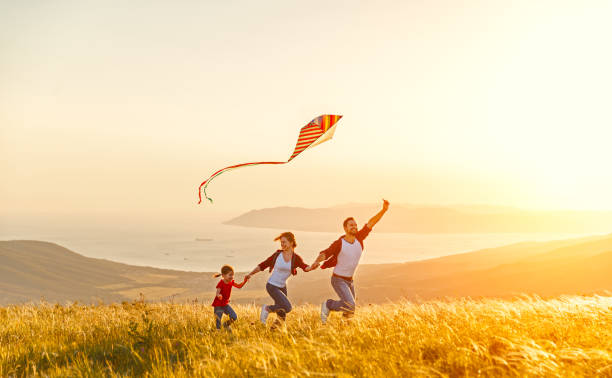 Happy family father of mother and child daughter launch a kite on nature at sunset stock photo