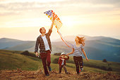 Happy family father of mother and child son launch a kite on nature at sunset