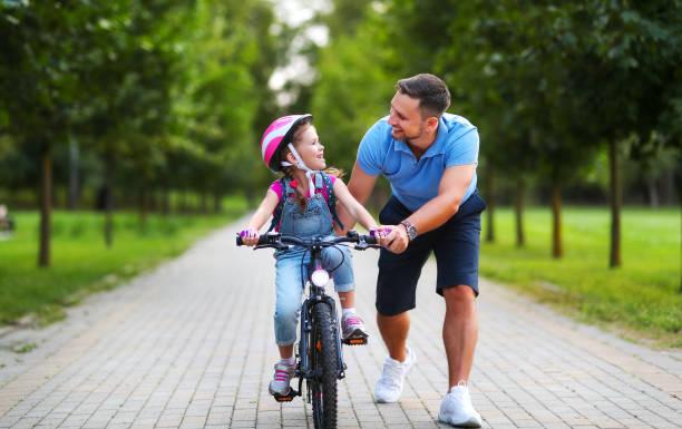 glücklicher Familienvater lehrt Kind Tochter, ein Fahrrad im Park zu fahren – Foto