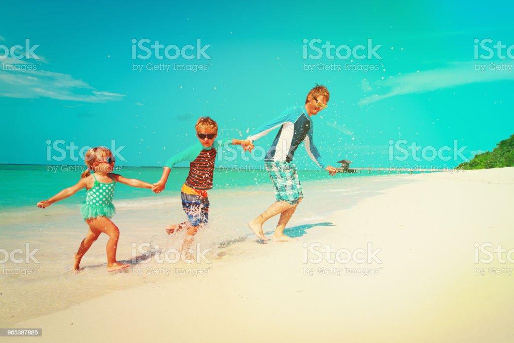 happy family -father with kids play with water run on beach zbiór zdjęć royalty-free
