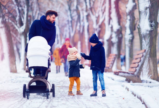 happy family, father with kids walking on the winter street stock photo