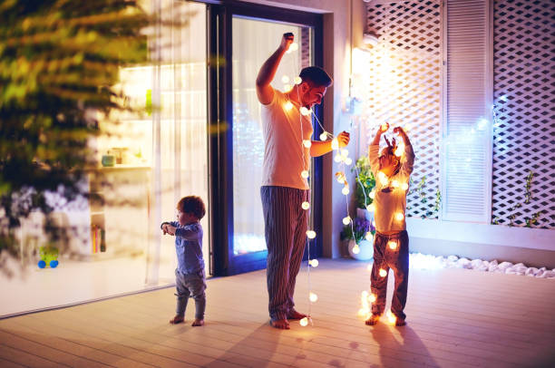 happy family, father with sons decorate open space patio area with christmas garlands stock photo
