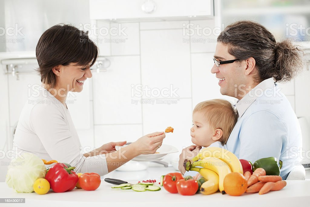 Happy family feeds a son with baby food royalty-free stock photo
