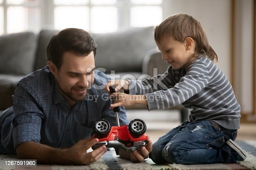 Funny little cute kid boy learning repairing toy vehicle with instruments, having fun with affectionate daddy, lying together on floor. Happy family fixing car, enjoying playtime together at home.