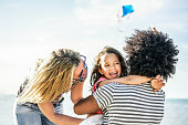 Happy family flying with kite and having fun on the beach - Multi ethnic couple playing with cheerful daughter on summer vacation - Travel,love,holidays concept - Focus on faces - Warm filter