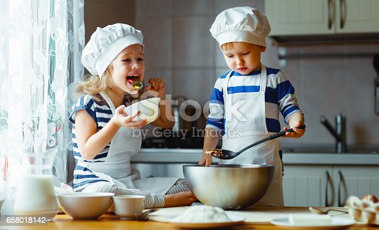 664420980 istock photo happy family funny kids bake cookies in kitchen 658018142