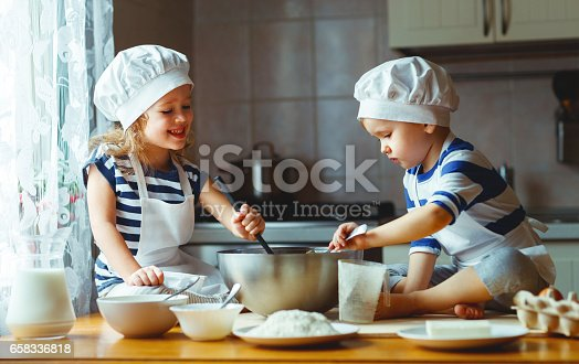 664420980 istock photo happy family funny kids bake cookies in kitchen 658336818