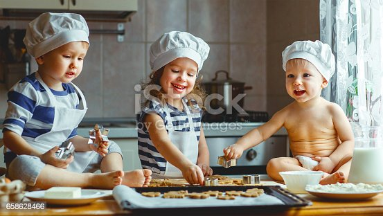 664420980 istock photo happy family funny kids bake cookies in kitchen 658628466