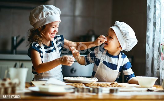 664420980 istock photo happy family funny kids bake cookies in kitchen 664417362