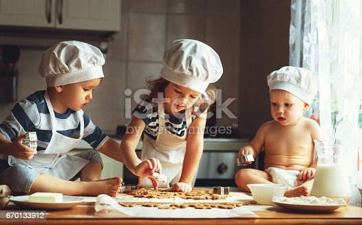 664420980 istock photo happy family funny kids bake cookies in kitchen 670133912