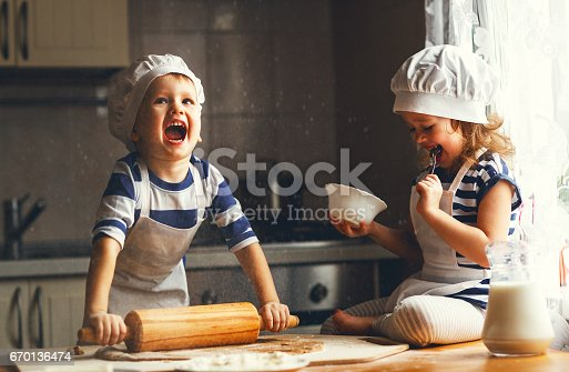 istock happy family funny kids bake cookies in kitchen 670136474