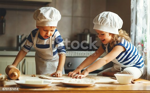 664420980 istock photo happy family funny kids bake cookies in kitchen 670137414