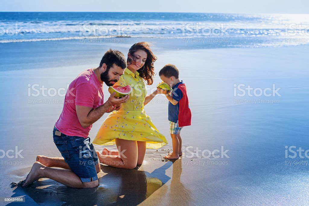 Happy family funny picnic on sand beach with sea surf stock photo