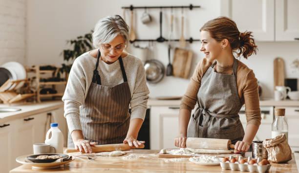 glückliche Familie Großmutter alte Mutter Schwiegermutter und Schwiegertochter Tochter kochen in der Küche, kneten Teig, backen Kekse – Foto