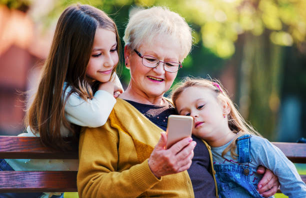 Happy family. Grandmother sitting in the park with granddaughters and having fun with smartphone. Lifestyle concept stock photo
