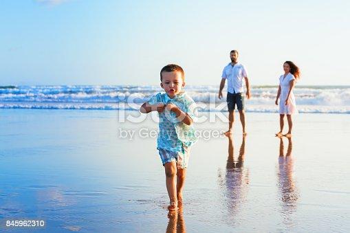 istock Happy family have fun on sunset beach 845962310