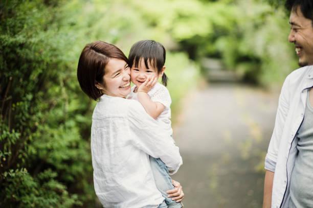 幸せな家族が屋外で女の赤ちゃんと楽しい時間を持っています。 - 母娘 笑顔 日本人 ストックフォトと画像